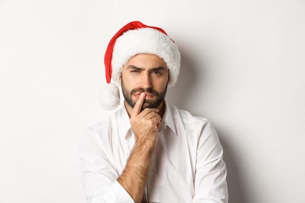 パーティー、冬休み、お祝いのコンセプト。サンタの帽子、白い背景を身に着けて、クリスマスと新年を考えている真面目な男。