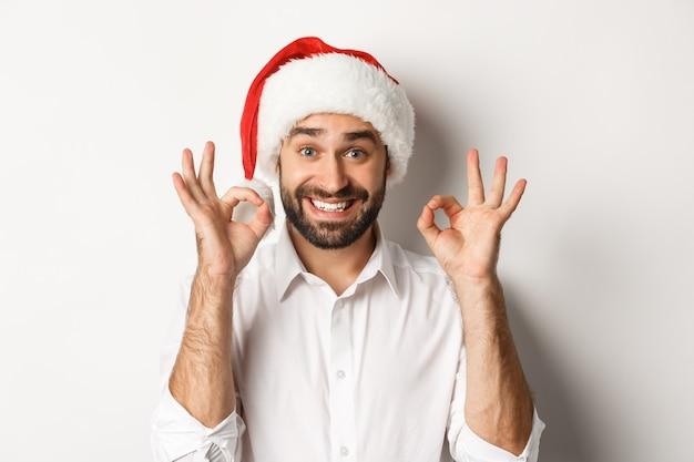 Festa, vacanze invernali e concetto di celebrazione. uomo gioioso che gode del natale e mostra il segno giusto, sorridendo soddisfatto, indossando il cappello della santa