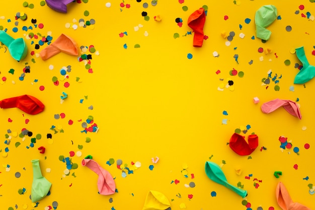 Party with confetti remnants and colorful balloons on yellow