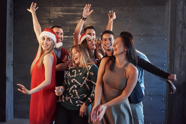 Party with friends. they love christmas. group of cheerful young people carrying sparklers and champagne flutes dancing in new year party and looking happy. concepts about togetherness lifestyle