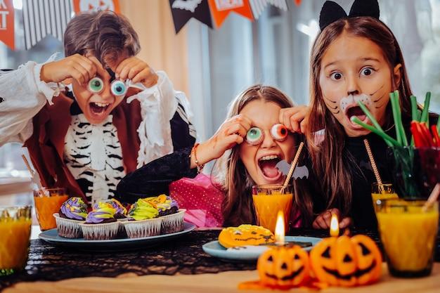お菓子とのパーティー。お菓子でハロウィンパーティーをしながら素晴らしい遊びのトリックを感じている3人のかわいい学童