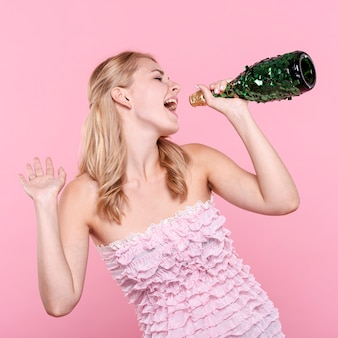 Party woman singing at champagne bottle