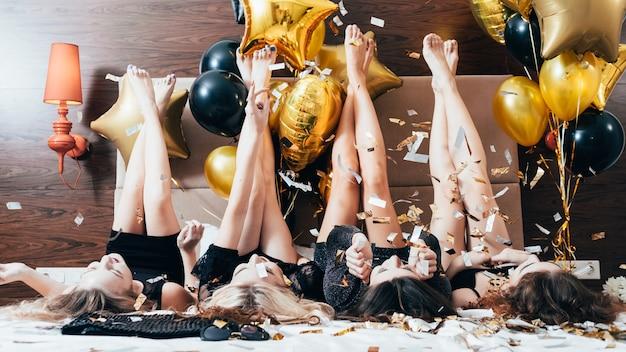 파티 여성. 재미와 기쁨. 반짝이 색종이와 풍선 장식. 블랙 침대 다리에 누워있는 젊은 여성. 축제 분위기.