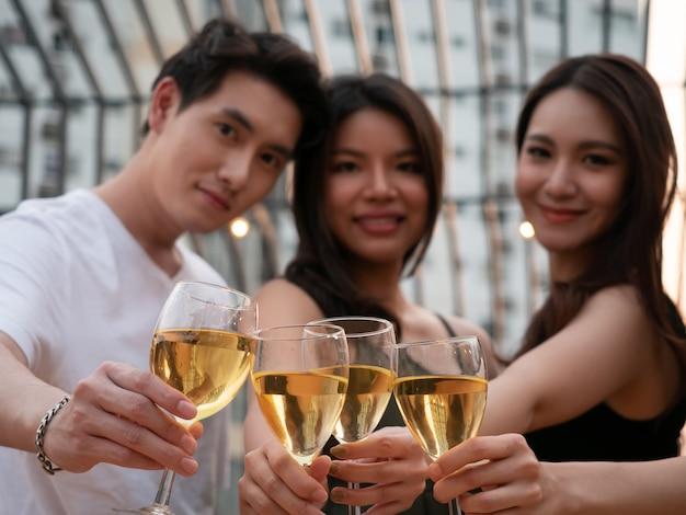 Группа в составе азиатский друг веселя и выпивая на террасе party. молодые люди поджаривают бокал вина в ресторане на крыше
