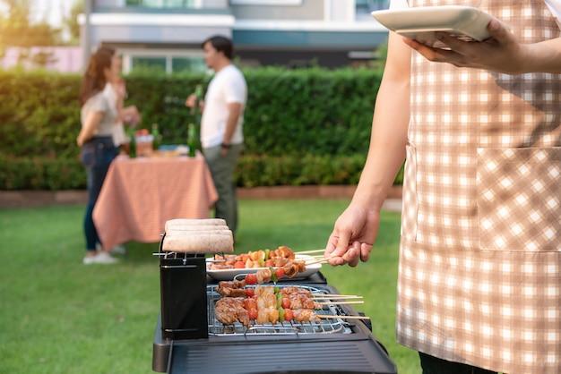 Азиатский человек варя гриль и сосиску барбекю для группы в составе друзья для еды party в саде дома.