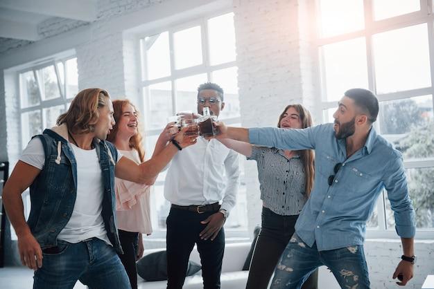 Вечеринки и празднование. молодые люди, хорошо проводящие время в офисе. улыбаясь и пить с окнами на фоне