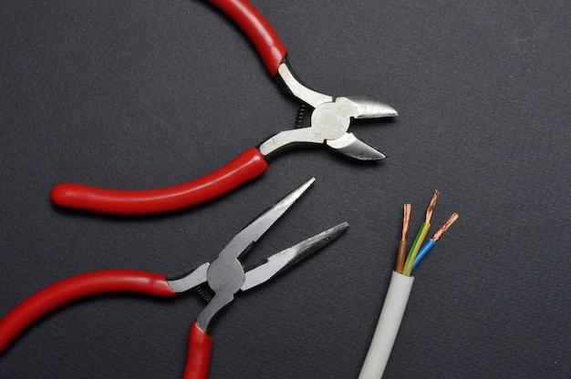 Pasatizhとワイヤーカッターは、剥がされた3芯ワイヤーで所定の位置にあります。暗い背景。