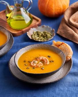 파세테리안 소박한 호박과 당근 크림 퓌레 수프, 새우 향신료와 토스트를 그릇에