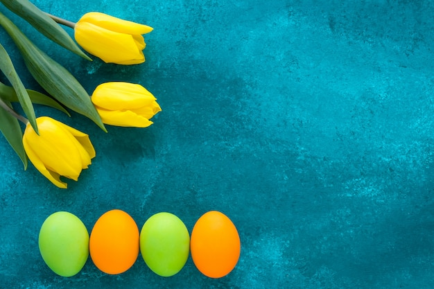 明るい塗られた卵とグランジ暗いターコイズブルーの背景に黄色のチューリップのパスカルギフトカード。コピースペースでお祝いイースターフレーム。