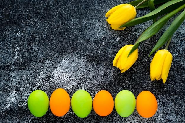 コピースペースを持つパスカルモックアップ。塗装卵とコンクリートの黒い背景に黄色のチューリップのお祝いイースターフレーム。