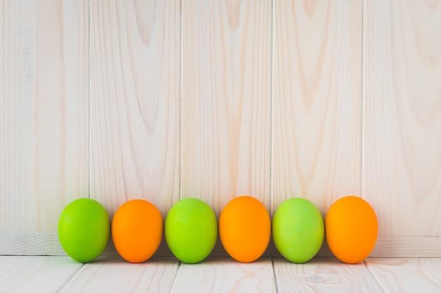 Пасхальный шаблон с пространством для текста. окрашенные пасхальные яйца на легких деревянных досках.
