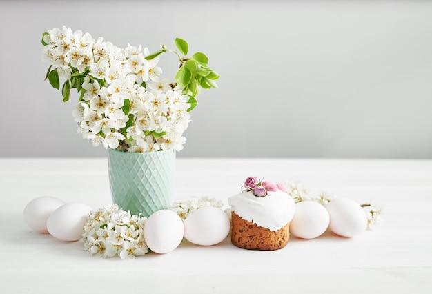 イースターの甘いパン、花とジンジャーブレッドのイースターケーキ。コピースペースを持つ休日朝食コンセプト。イースターのグリーティングカードテンプレート。自家製のpasques。白いテーブルにイースターのお菓子。