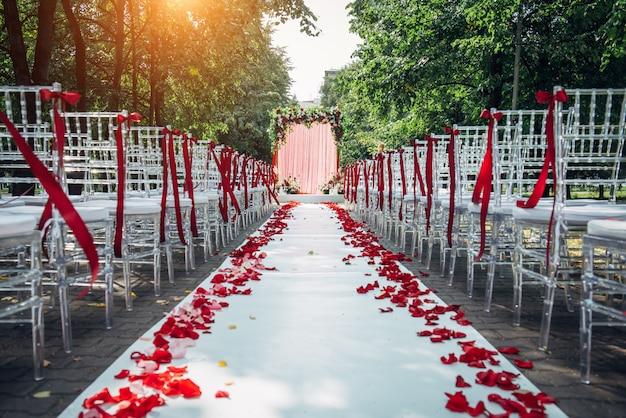 Проход между стульями, украшенными лепестками роз, ведет к свадебной арке. торжественное свадебное оформление в парке среди зеленых деревьев.