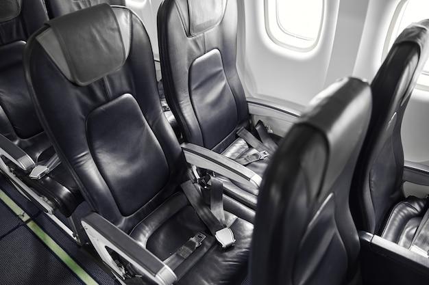 Пассажирские места в салоне современного реактивного пассажирского самолета. пустой интерьер. кожаные кресла с ремнями. гражданская коммерческая авиация. концепция путешествия по воздуху