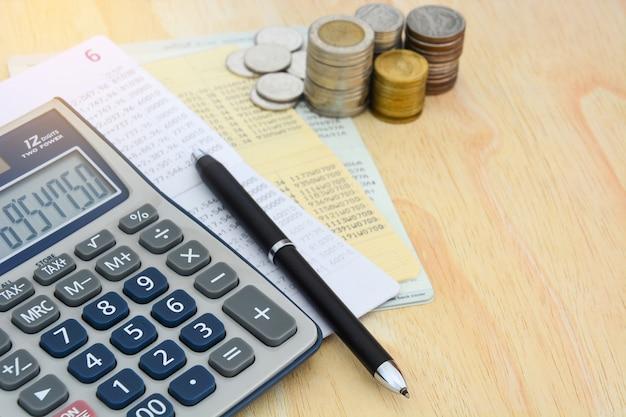 通帳保存アカウント、電卓、ペン、木製のテーブル背景にコインの山