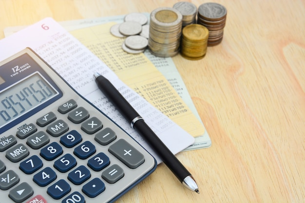 Passbooks saving account, calculator, pen and pile of coins on wooden table background