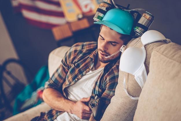 멋진 파티 후 기절. 지저분한 방에 있는 소파에서 낮잠을 자는 맥주 모자를 쓴 젊고 잘생긴 남자