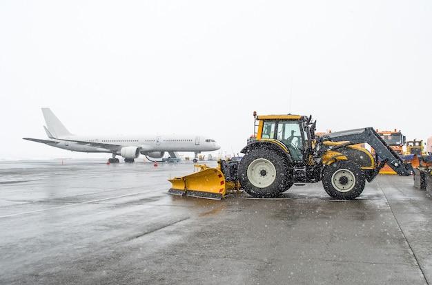 駐車場の旅客機と冬の雪の降る天候のスノートラクター。