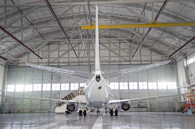 Passenger aircraft on maintenance of engine and fuselage repair in airport hangar. rear view of the tail.