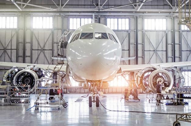 空港格納庫でのエンジンのメンテナンスと胴体の修理に関する旅客機。