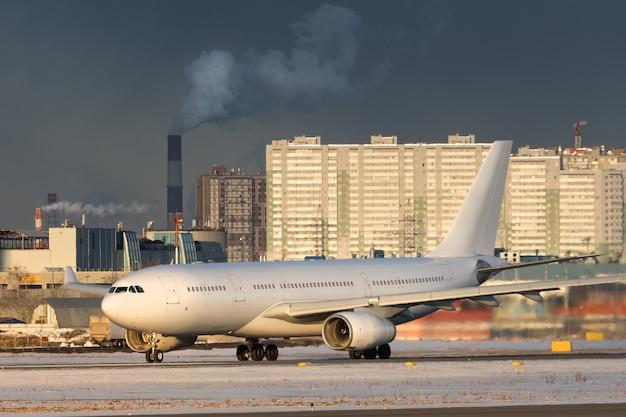 冬の日の夕暮れ時に離陸する旅客機。飛行機が滑走路をオンにします。