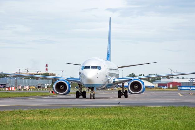 アスファルトの空港のエプロンでタキシングしている旅客機は、目に見えるマーキングです。