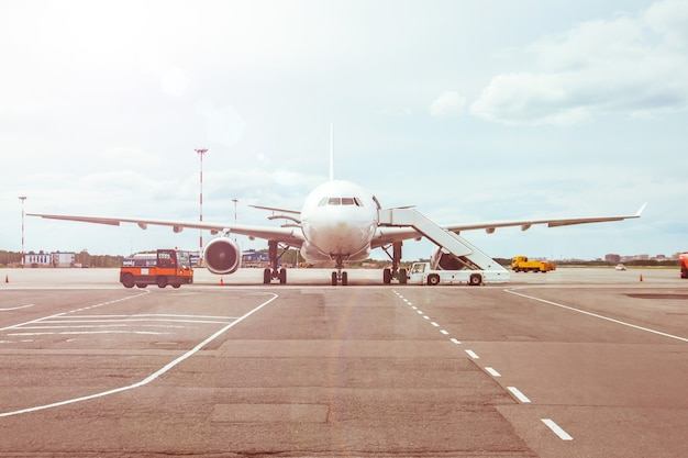 Passenger aircraft, waiting for the passengers to board at the airport terminal.