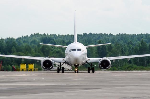 機首を前にして空港の駐車場にある旅客機。