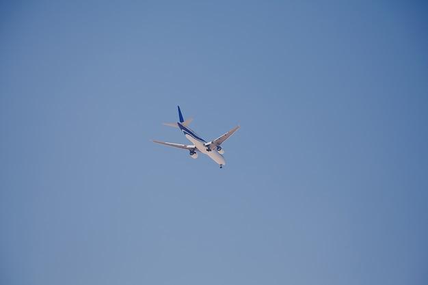 Passenger airplane landing against blue sky