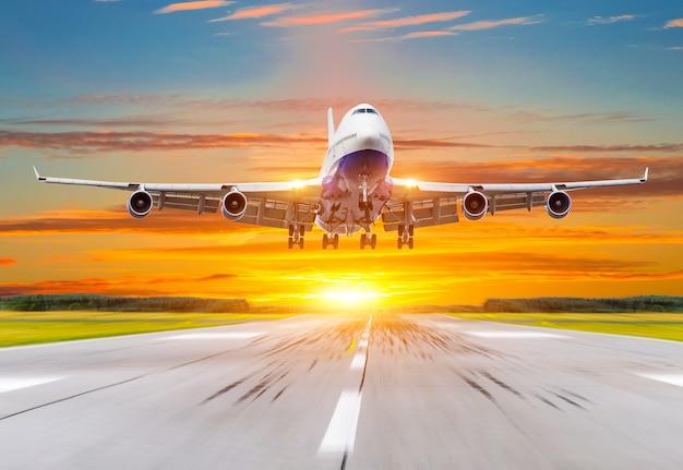 Passenger airplane landing at sunset on a runway.