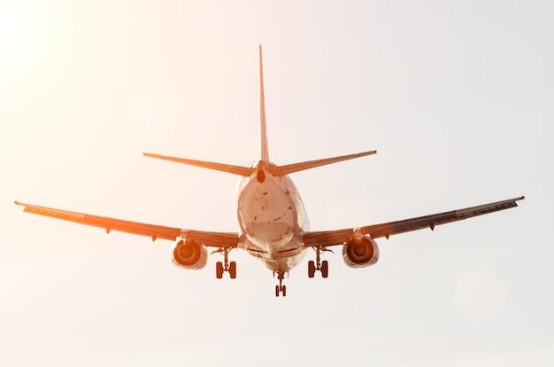 Passenger airplane landing in sunset sky airport.