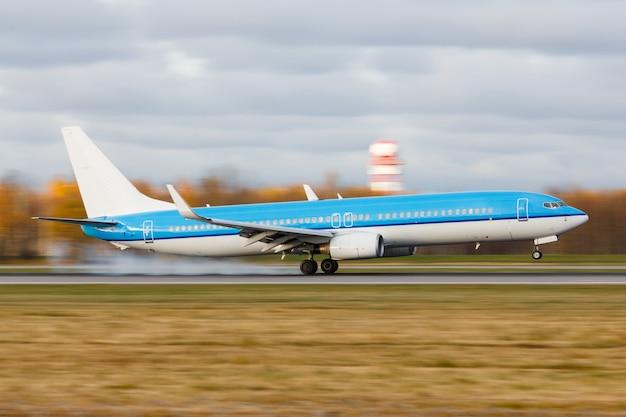 夕暮れ時の空港の滑走路にタッチダウンで着陸する旅客機