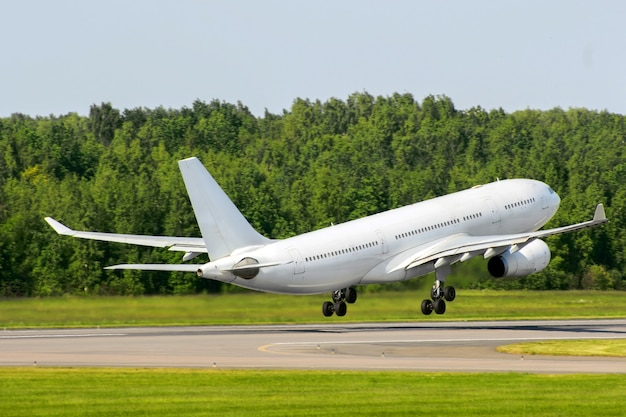 Passenger airplane take off against the background of a green forest