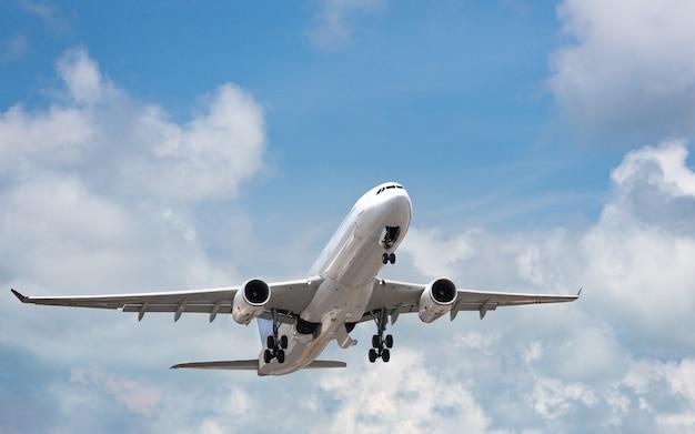 明るい曇り空で離陸する旅客機。青空に浮かぶワイドボディの民間旅客機。休暇、航空、旅行の概念