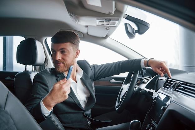 Passeggero sul sedile posteriore. uomo d'affari moderno che prova la sua nuova automobile nel salone dell'automobile