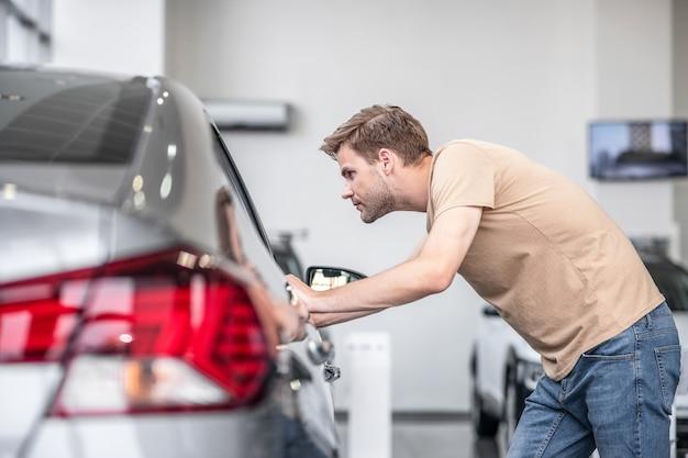 Легковой автомобиль. молодой человек в футболке и джинсах трогает руками, заглядывая в окно нового серого автомобиля в автосалоне