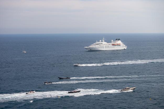たくさんのパワーボートに囲まれた晴れた日の海での客船