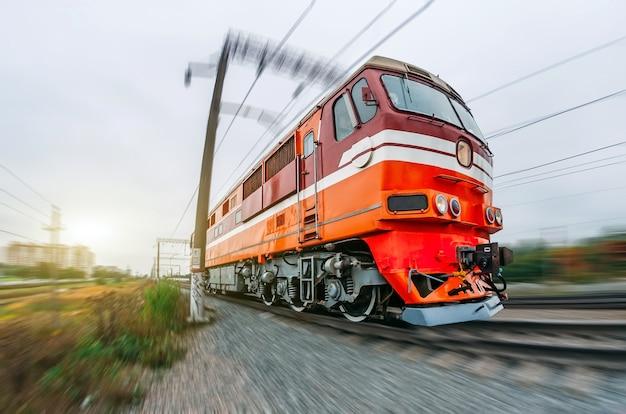 Пассажирский дизель-поезд едет на скорости железнодорожных вагонов налегке.
