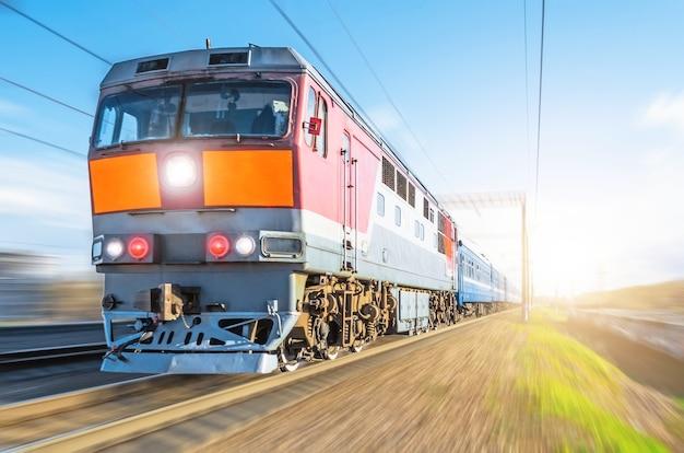 Пассажирский дизельный поезд, едущий на скорости, железнодорожные вагоны, путешествуют на закате.