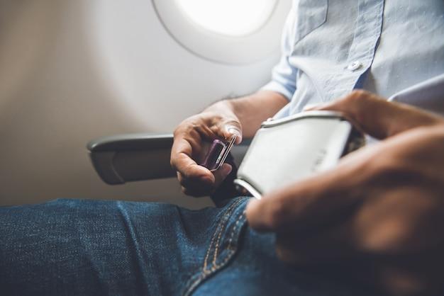 Passenger fastening seat belt while sitting on the airplane