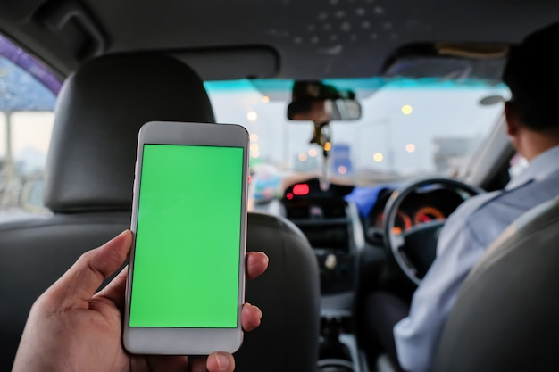 Пассажир на заднем сиденье такси со смартфоном в руке для использования мобильного приложения.