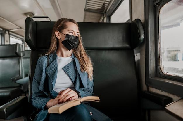 Пассажир в поезде в медицинской маске и смотрит в окно