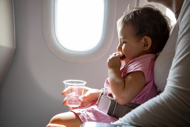 Passenger infant sits in airplane wearing seat belt in mother arms and eats cookies safe travel