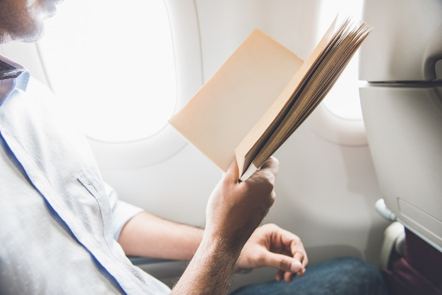 Passenger killing time by reading book while traveling on the plane
