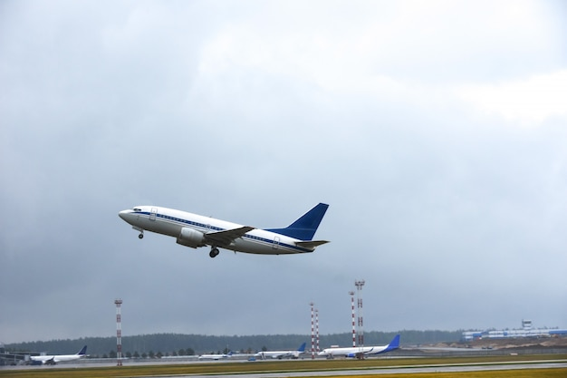Passenger liner takes off into the sky from the airport runway in cloudy weather with rain