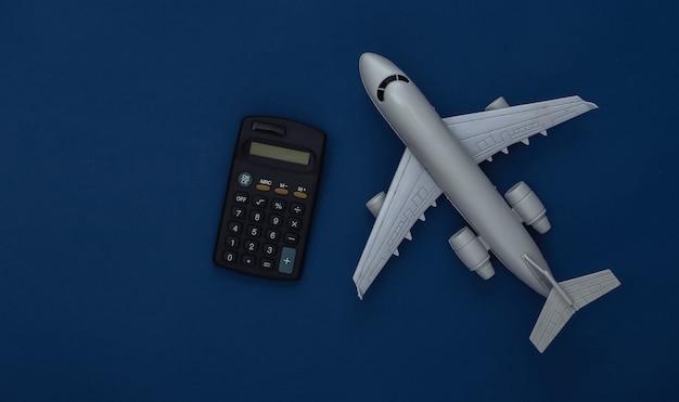 Фигурка пассажирского самолета и калькулятор на классическом синем фоне. расчет стоимости авиаперелета. цвет 2020. вид сверху.