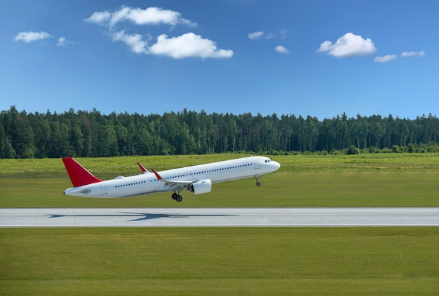 Passenger plane takes off from airport runway in forest. Premium Photo