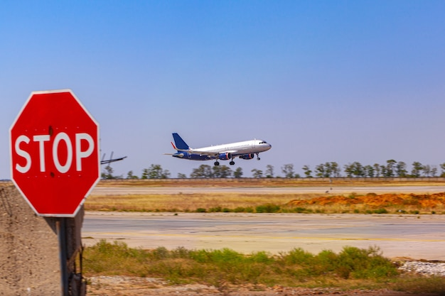Passenger plane taking off from runway at airport on sunny day