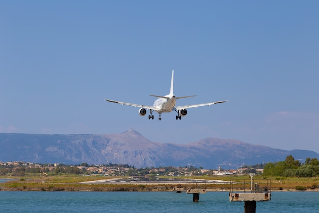 乗客の飛行機がケルキラ空港に着陸しています。ギリシャ、コルフ島。高さの減少、クローズアップ。山と海を背景に滑走路。