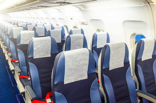 Passenger seat, interior of airplane with passengers sitting on seats.